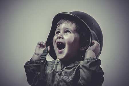 military uniform: uniform, fun and funny child dressed in military cap, playing war games