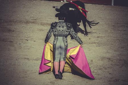 sand, bullfight, traditional Spanish party where a matador fighting a bull photo