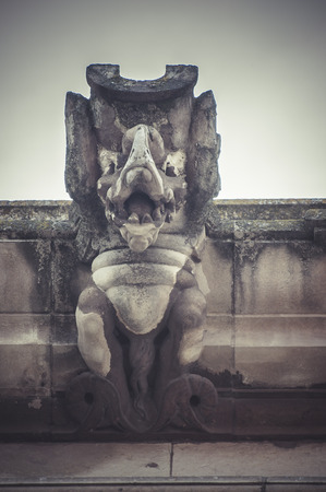Devil, Stone gargoyle on the facade of the University of Alcala de Henares, Madrid Spain photo