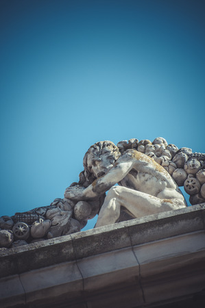 Man, Stone gargoyle on the facade of the University of Alcala de Henares, Madrid Spain photo