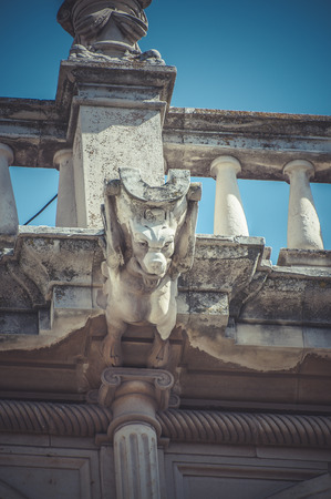 Scary, Stone gargoyle on the facade of the University of Alcala de Henares, Madrid Spain photo