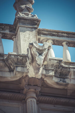 Statue, Stone gargoyle on the facade of the University of Alcala de Henares, Madrid Spain photo