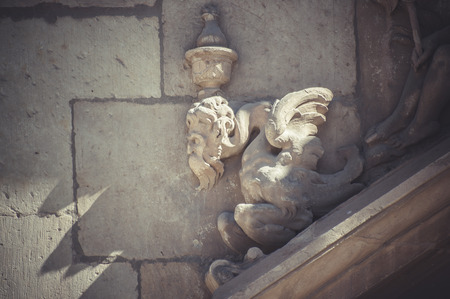 Sculpture, Stone gargoyle on the facade of the University of Alcala de Henares, Madrid Spain photo