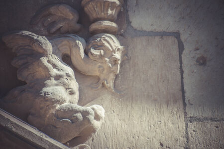 Old, Stone gargoyle on the facade of the University of Alcala de Henares, Madrid Spain photo