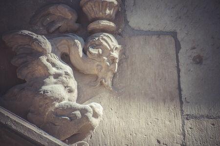 Old, Stone gargoyle on the facade of the University of Alcala de Henares, Madrid Spain photo