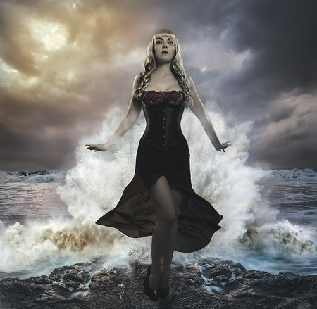 the forces of nature, blonde woman on the rocks with the sea raging and powerful Stock Photo