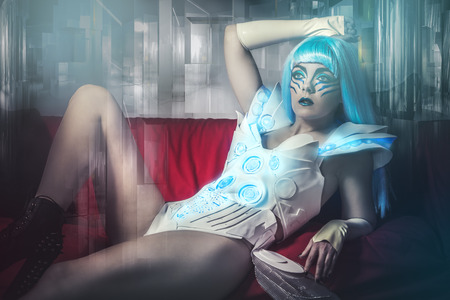 beautiful with blue hair and futuristic armor lying on a red couch photo