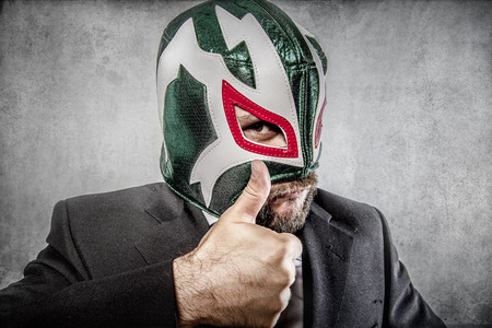 all it is ok, aggressive executive suit and tie, Mexican wrestler mask Standard-Bild