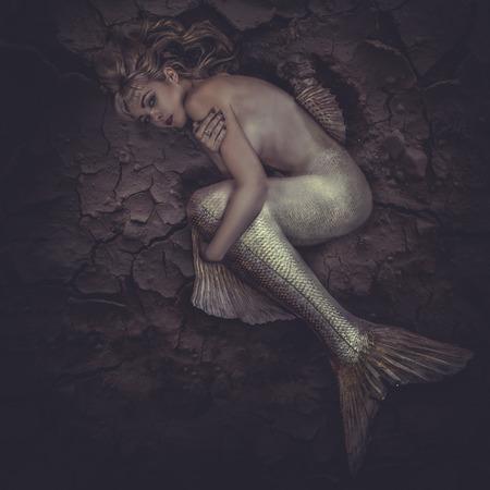 Meerjungfrau in einem Meer von Schlamm gefangen, Konzept Fantasie Fisch Frau mit den schönen blonden Haaren und ihren Körper Skalen Standard-Bild