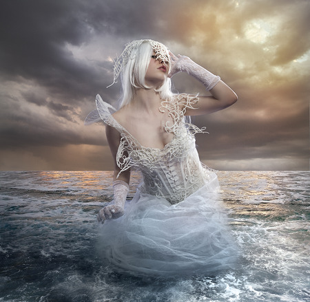 sexy angel: the forces of nature, blonde woman on the rocks with the sea raging and powerful Stock Photo