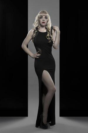 model pose: hermosa rubia con vestido largo negro de modelo profesional plantean