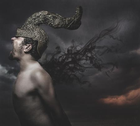 hombre asustado: miedo, el hombre con el casco de cuernos de oro pesadillas concepto Foto de archivo