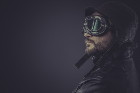 aeronautical: portrait pilot dressed in vintage style leather cap and goggles