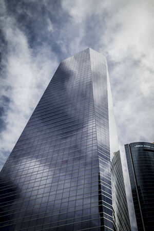 success, skyscraper with glass facade and clouds reflected in windows photo