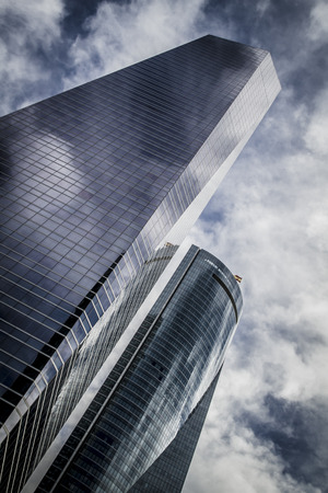 skyscraper with glass facade and clouds reflected in windows photo