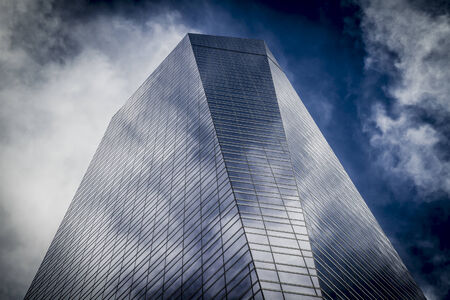 modern, skyscraper with glass facade and clouds reflected in windows