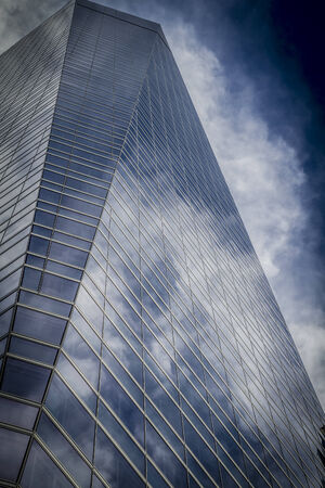 business, skyscraper with glass facade and clouds reflected in windows