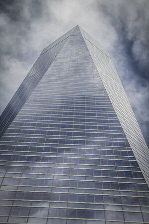 futuristic, skyscraper with glass facade and clouds reflected in windows