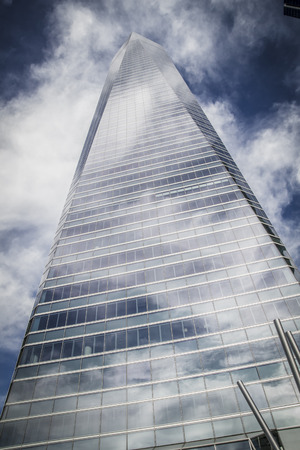 skyscraper with glass facade and clouds reflected in windows