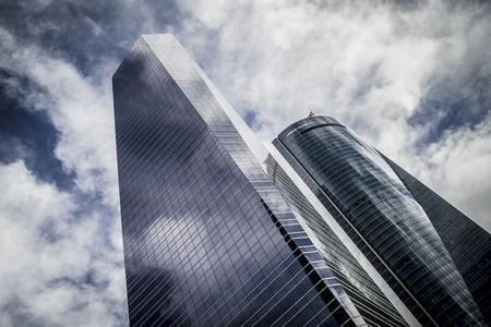 steel, skyscraper with glass facade and clouds reflected in windows photo
