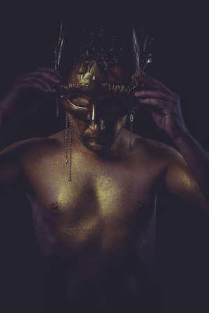 golden bodypaint, man with gold helmet, ancient warrior deity photo
