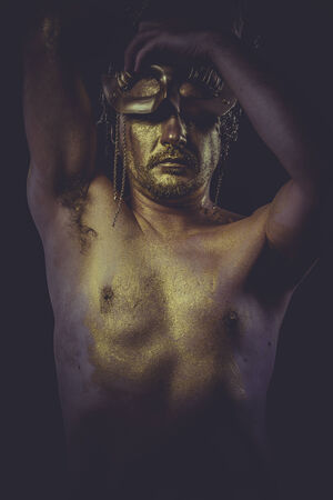 painted golden bodypaint, man with gold helmet, ancient warrior deity photo