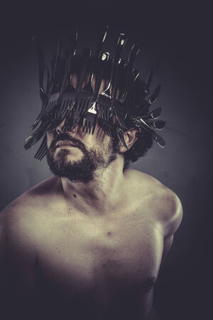 Man with helmet made of forks and knives, concept photo