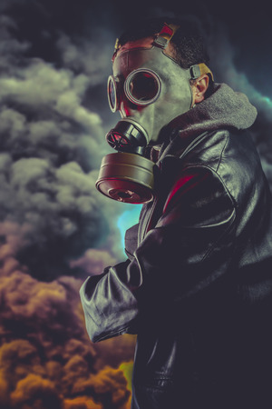 Armed man with gas mask over explosion background photo
