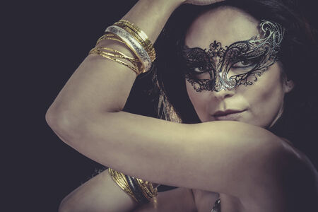 Sexy woman with  venetian mask and gold and silver bracelets photo