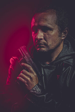 Robber with gun over red background photo