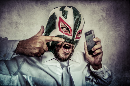 man arguing by phone, aggressive executive suit and tie, Mexican wrestler mask Archivio Fotografico