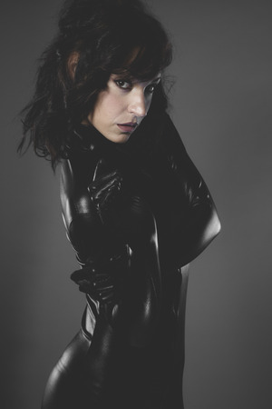 war, sexy woman dressed in black latex, future concept and new technologies photo