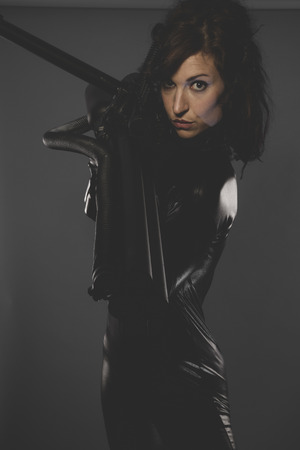 modern, sexy woman dressed in black latex, future concept and new technologies photo
