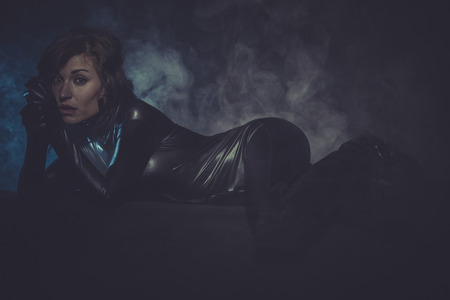 cyber war: sexy woman dressed in black latex, future concept and new technologies Stock Photo
