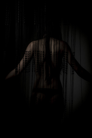 night, nude woman back through a curtain wire