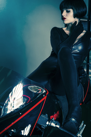 Sensual brunette woman in modern motorcycle design and aggressive photo