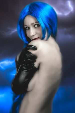 electric storm: vogue style portrait of beautiful delicate woman with blue hair over electric storm