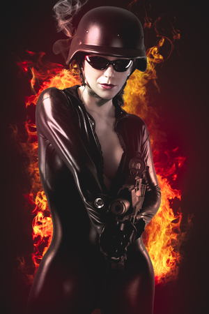 sexy brunette woman: Sexy brunette woman in latex jumpsuit with heavy gun and helmet over fire background