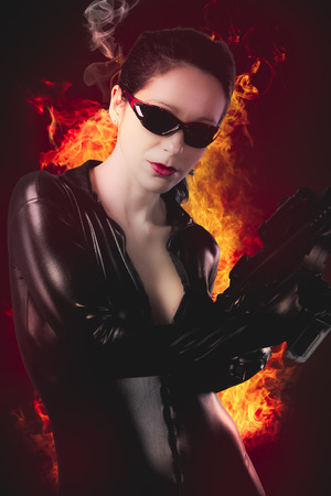 woman with gun: Sexy brunette woman in latex jumpsuit with heavy gun over fire background