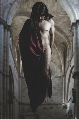 Nude magician levitating inside a Gothic cathedral