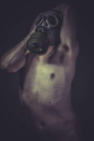 Industrial, concept of risk of contamination, naked man with gas mask photo