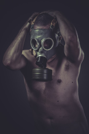 Biohazard, concept of risk of contamination, naked man with gas mask photo