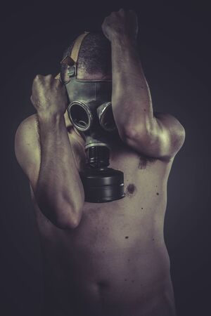 concept of risk of contamination, naked man with gas mask photo