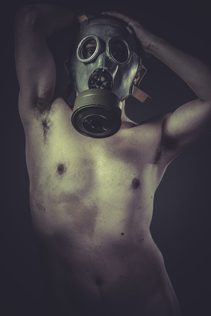 Pollution, concept of risk of contamination, naked man with gas mask photo