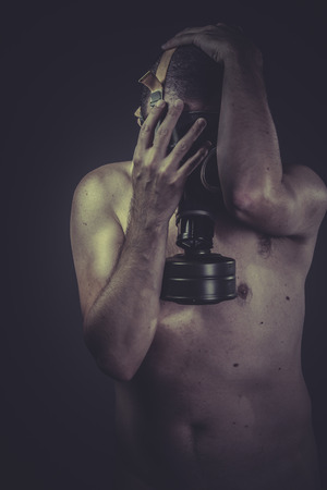 Epidemic, concept of risk of contamination, naked man with gas mask photo
