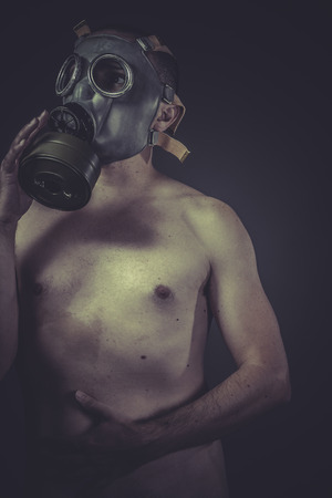 Danger, concept of risk of contamination, naked man with gas mask photo