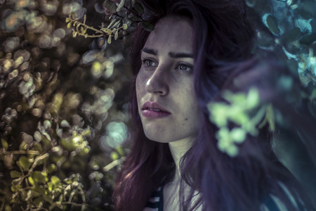 female face closeup: Feeling blue, melancholy young girl in a forest with sad gesture Stock Photo