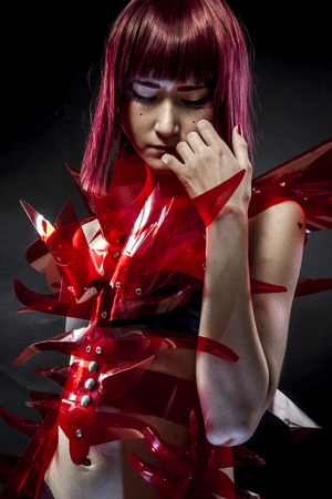 japanese woman: geisha robot with red armor, beautiful young Japanese woman in a suit methacrylate Stock Photo