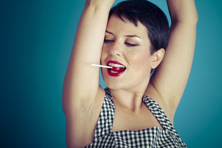 sugarplum: Eat, happy young woman with lollypop  in her mouth on blue background Stock Photo