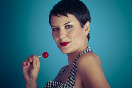 sugarplum: Lolly, happy young woman with lollypop  in her mouth on blue background